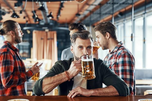 Jovem encantador em roupas casuais bebendo cerveja enquanto passa um tempo com os amigos no bar
