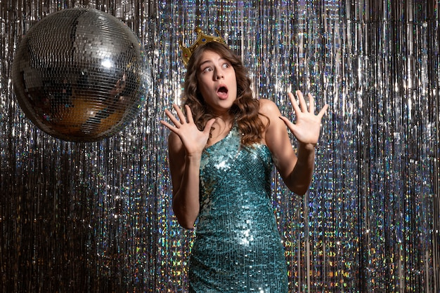 Jovem encantadora assustada usando vestido azul verde brilhante com lantejoulas com coroa na festa