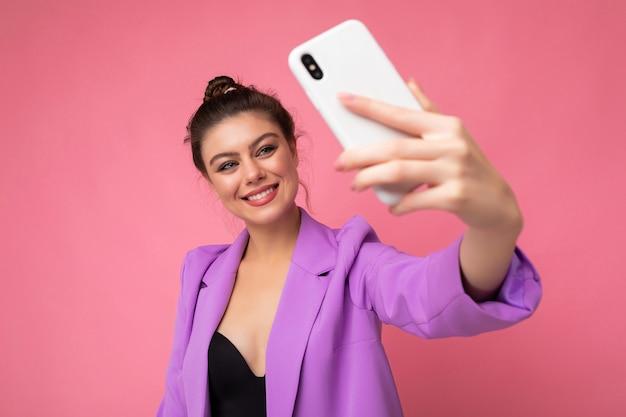 Jovem encantadora atraente sorridente feliz segurando e usando telefone celular, tirando selfie vestindo