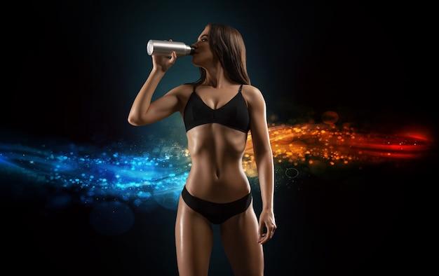 Jovem encantadora bebe aminoácidos de um shaker. conceito de musculação. mídia mista