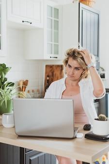 Jovem encantadora com laptop trabalhando em casa na cozinha