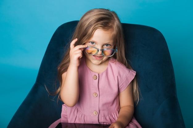 Jovem encantadora com óculos, sentada na cadeira com um tablet, imitando um professor em uma parede azul
