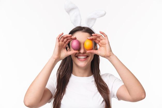 Jovem encantadora com orelhas de coelho segurando um ovo colorido