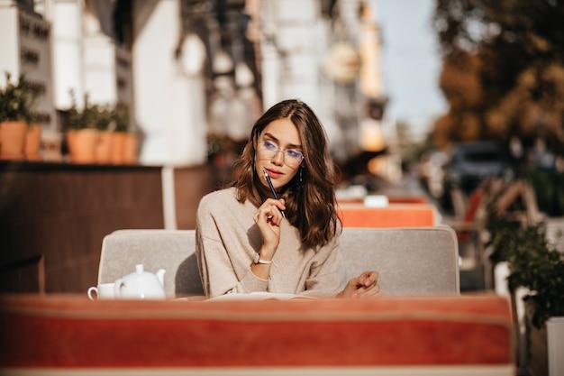 Jovem encantadora com penteado ondulado moreno, lábios vermelhos e óculos elegantes, blusa bege, estudando atentamente no terraço do café da cidade em um dia quente de outono