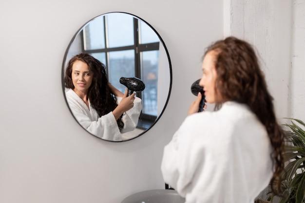 Jovem encantadora com secador de cabelo cuidando de seus longos cabelos escuros ondulados em frente ao espelho do banheiro