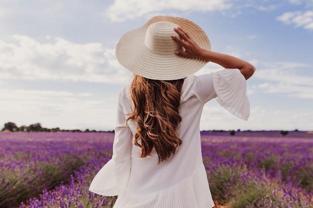 Jovem encantadora com um chapéu e vestido branco em um campo de lavanda roxo ao pôr do sol