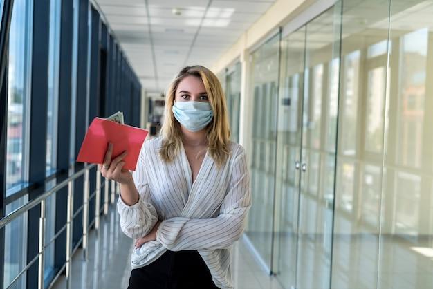 Jovem encantadora com uma máscara médica segurando um envelope com dinheiro no shopping. conceito de finanças