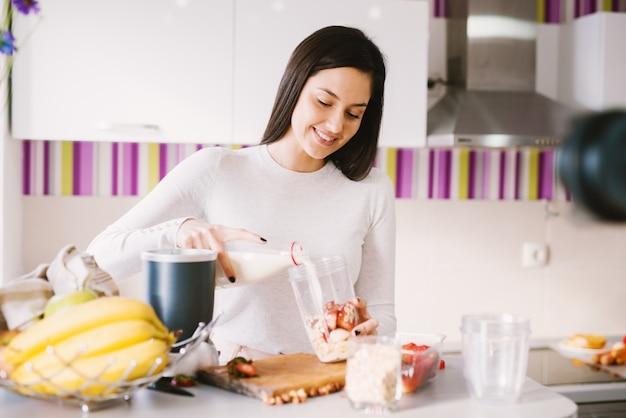 Jovem encantadora e alegre está derramando leite em uma tigela cheia de frutas e está preparando cereais em pé perto do balcão da cozinha cheio de frutas.