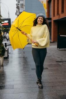 Jovem encantadora e encaracolada usando guarda-chuva amarelo na rua da cidade de megapolis em dia chuvoso