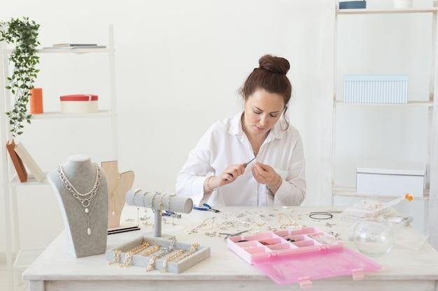 Jovem encantadora e entusiasmada fazendo bijuterias exclusivas