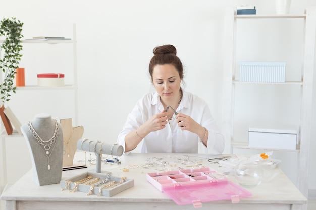 Jovem encantadora e entusiasmada mulher caucasiana fazendo belas bijuterias exclusivas enquanto está sentado no
