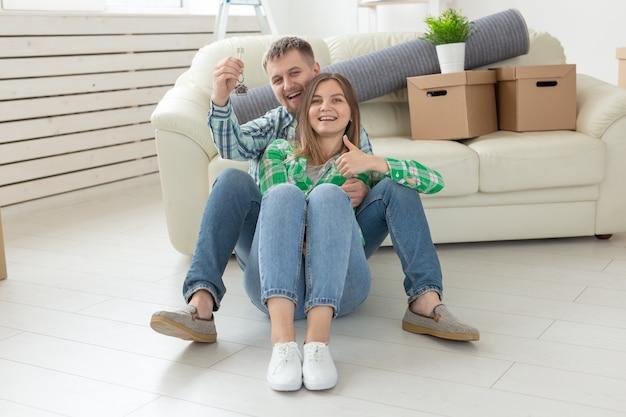 Jovem encantadora e seu marido segurando nas mãos as chaves de seu novo apartamento enquanto estão sentados