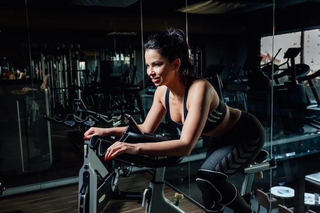 Jovem encantadora em roupas esportivas, sorrindo e sentada na moderna bicicleta ergométrica perto do espelho em um elegante ginásio