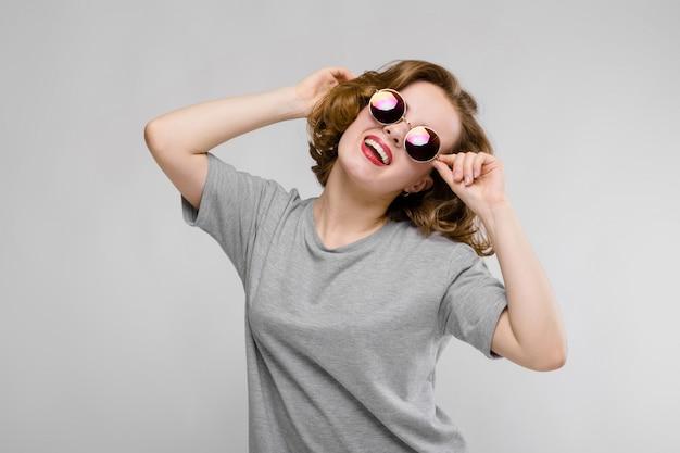 Jovem encantadora em uma camiseta cinza sobre um fundo cinza. menina alegre em copos redondos