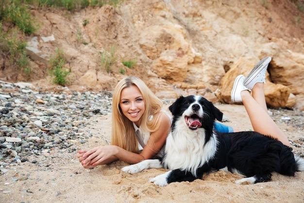 Jovem encantadora feliz com cachorro na praia