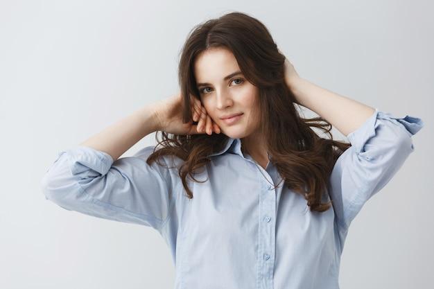 Jovem encantadora garota com belos cabelos escuros na camisa azul, segurando as mãos no cabelo com um sorriso suave e gentil.