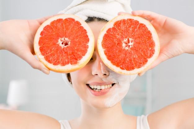 Jovem encantadora garota mordendo os lábios, tem máscara fasial branca, detém duas fatias de laranja, tem uma toalha branca na cabeça. cosméticos naturais, skincare, bem-estar, tratamento facial, conceito de cosmetologia.