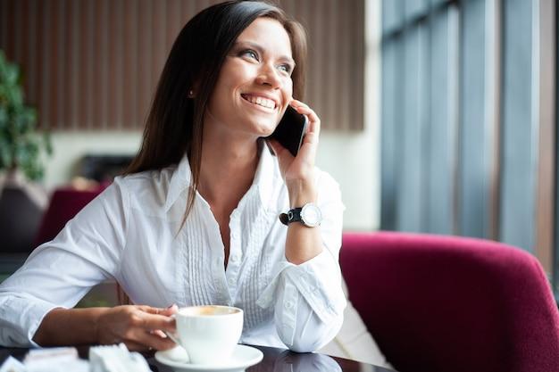 Jovem encantadora ligando com o smartphone enquanto está sentada sozinha em um café durante o tempo livre