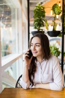 Jovem encantadora ligando para o celular enquanto está sentada sozinha no café durante o tempo livre, mulher atraente com um sorriso fofo, conversando com o celular enquanto descansa no café