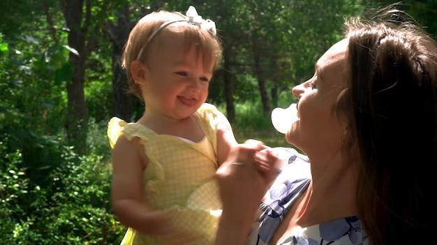 Jovem encantadora mãe se divertindo com sua filha no jardim