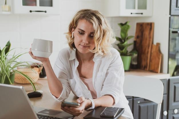 Jovem encantadora na cozinha bebe café e usa smartphone