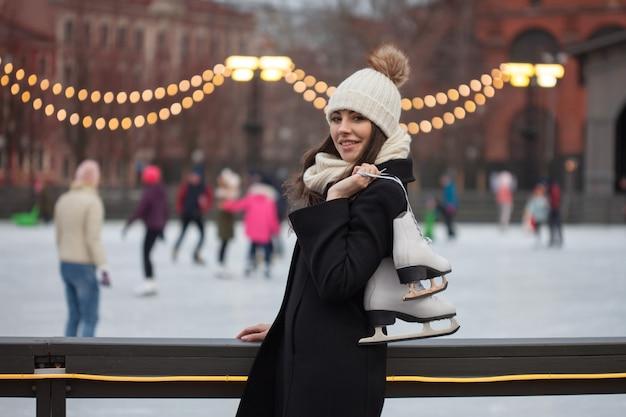Jovem encantadora no parque perto da pista de gelo.