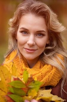 Jovem encantadora posando com folhas amareladas caídas na frente, caminhando pelo jardim de outono amarelo