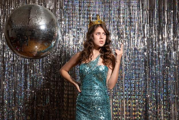 Jovem encantadora preocupada com vestido azul esverdeado brilhante com lantejoulas e coroa na festa