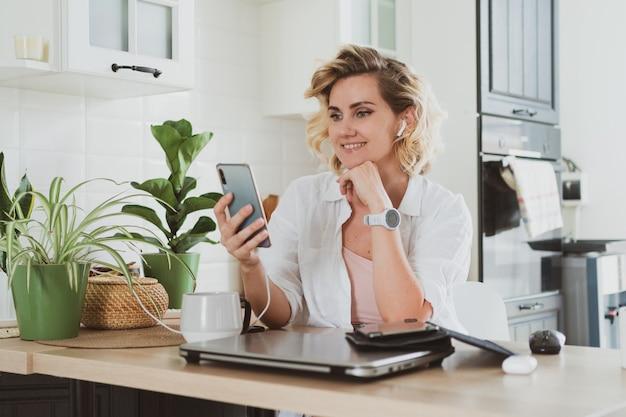 Jovem encantadora usa smartphone em casa na cozinha