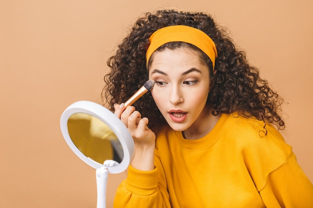 Jovem encaracolada alegre é sapplying creme de fundação em sua pele. ela está olhando para o espelho na mão. isolado em fundo bege