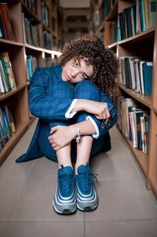 Jovem encaracolada linda de óculos e terno azul, sentado com os livros na biblioteca.