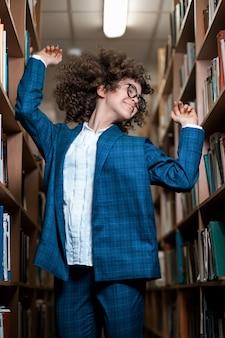 Jovem encaracolada linda de óculos e um terno azul está de pé na biblioteca