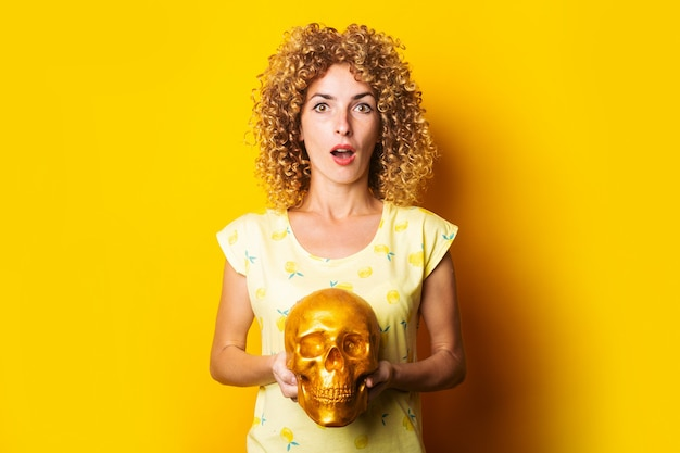 Jovem encaracolada surpresa segurando uma caveira dourada sobre fundo amarelo.