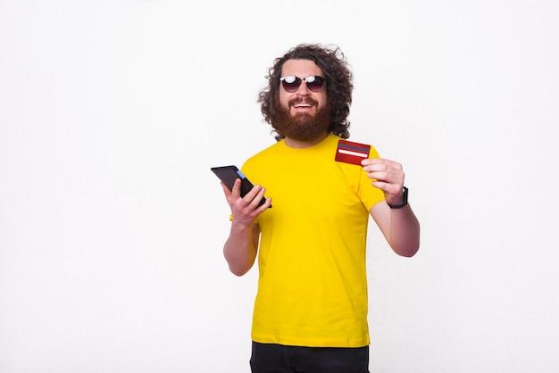 Jovem encaracolado está segurando seu cartão e tablet sobre fundo branco.