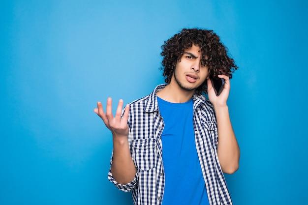 Jovem encaracolado falando ao telefone isolado na parede azul