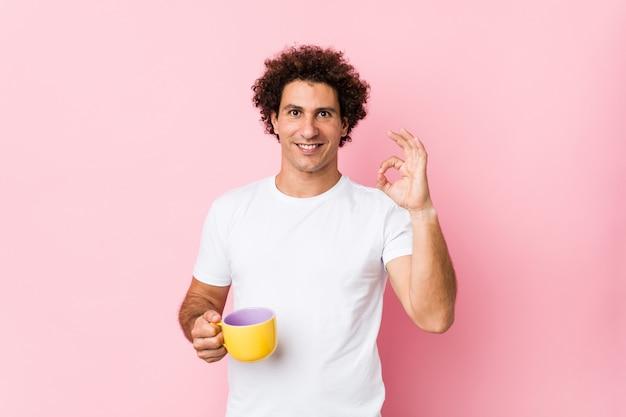 Jovem encaracolado segurando uma xícara de chá alegre e confiante mostrando okey gesto