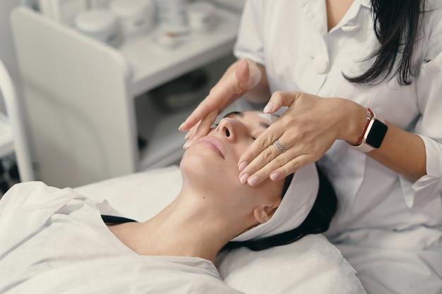 Jovem encontra-se com os olhos fechados, procedimento de tomada de cosmetologista