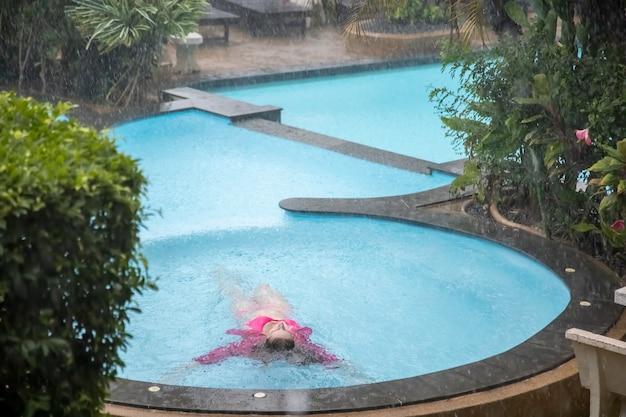 Jovem encontra-se na água de uma piscina tropical ao ar livre sob uma chuva torrencial.