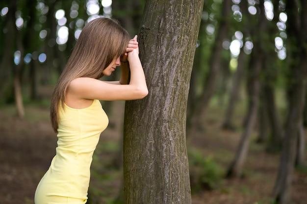 Jovem encostada no tronco de uma árvore na floresta de verão