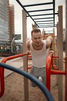Jovem enérgico faz exercícios ao ar livre na praça do esporte para manter o corpo em forma.