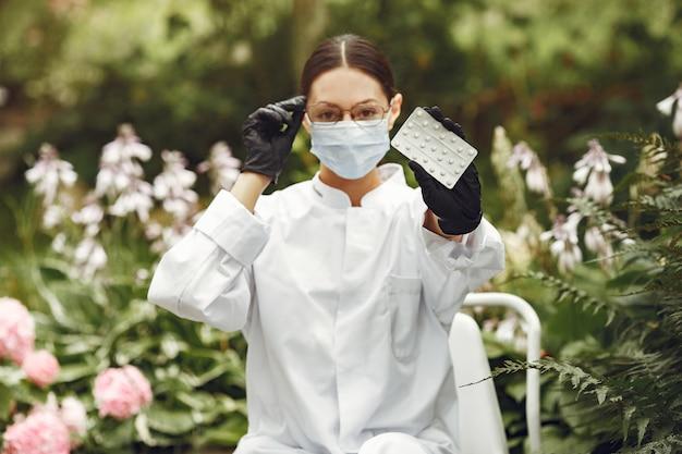Jovem enfermeira ao ar livre. médica da mulher. médico com comprimidos nas mãos.