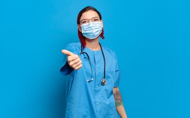 Jovem enfermeira atraente ruiva, sentindo-se orgulhosa, despreocupada, confiante e feliz, sorrindo positivamente com o polegar para cima.