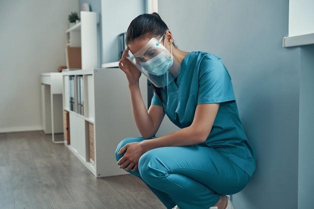 Jovem enfermeira cansada em trajes de trabalho de proteção, tocando a cabeça enquanto trabalhava no hospital