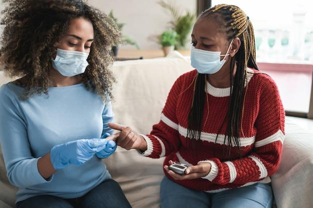 Jovem enfermeira colhendo sangue de paciente sênior para exame de diabetes em casa