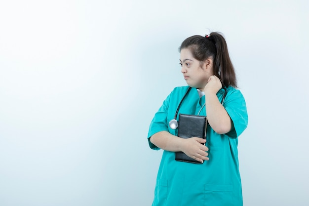 Jovem enfermeira com estetoscópio segurando o bloco de notas contra a parede branca.