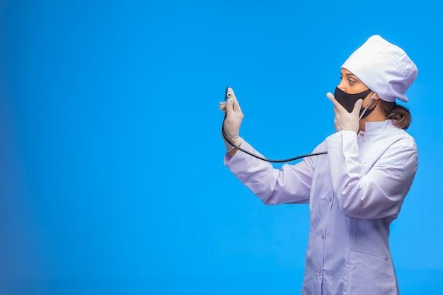 Jovem enfermeira com máscara facial preta verifica o paciente com estetoscópio enquanto cobre sua boca.