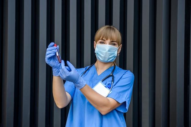 Jovem enfermeira com máscara médica apontando para uma sonda de sangue em laboratório