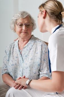 Jovem enfermeira consolando e cuidando de paciente idoso no hospital