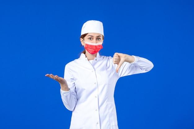 Jovem enfermeira de frente para um terno médico com máscara protetora vermelha na parede azul