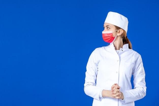 Jovem enfermeira de frente para um terno médico com máscara vermelha na parede azul